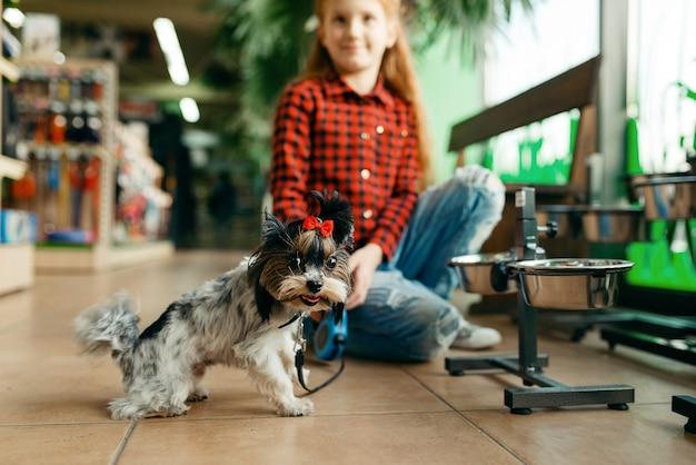 Menina procurando roupas para seu cachorro na loja de animais. criança comprando equipamentos em petshop, acessórios para animais domésticos