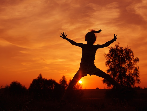 Menina pulando ao pôr do sol