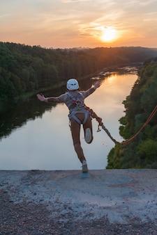 Menina pulando da ponte. uma mulher com um tempo incrível está envolvida no estilo livre no bungee jumping. uma jovem executa um truque reverso no bungee jumping. ir ao pôr do sol extreme young.