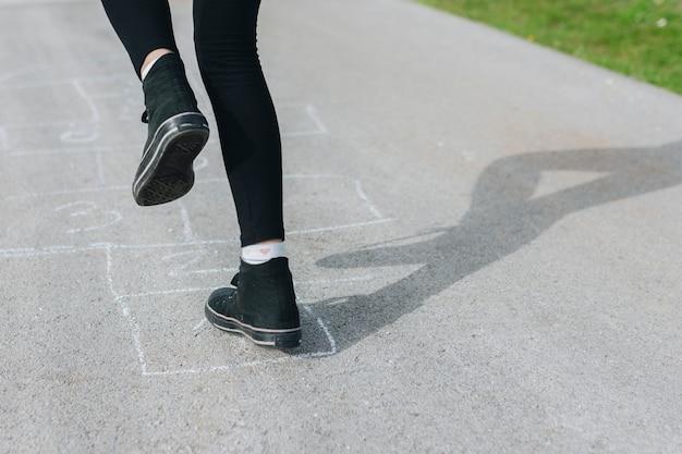 Menina pulando em caixas de giz desenhadas no asfalto