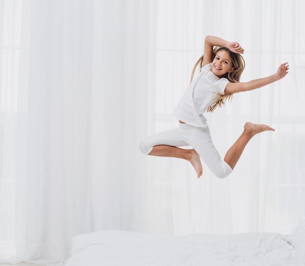 Menina pulando enquanto olha para a câmera