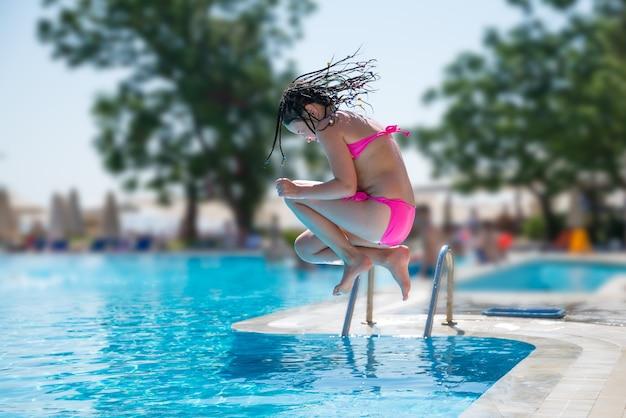 Menina pulando na piscina