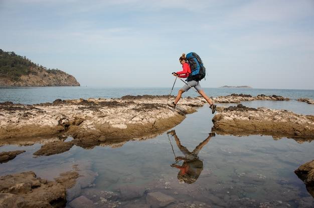 Menina pulando nas rochas no mar com mochila de caminhadas