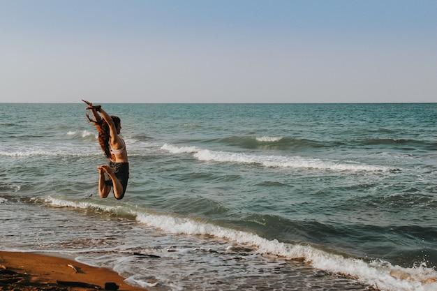 Menina pulando no ar na praia. conceito de verão.