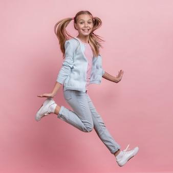 Menina pulando para o lado e ser feliz