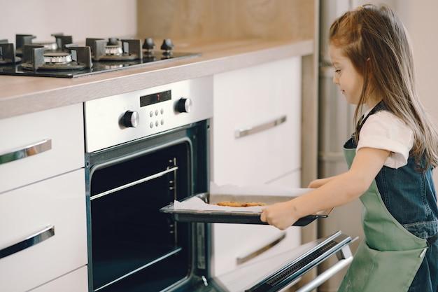 Menina puxa uma bandeja de biscoitos do forno