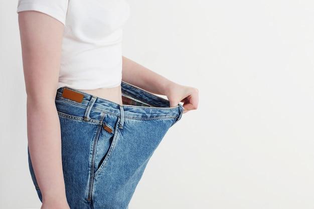 Menina puxando seus jeans grandes e mostrando a perda de peso