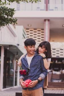 Menina que abraça um homem de atrás e isso prende rosas e um presente