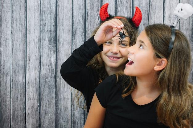 Menina que alimenta a aranha ao amigo