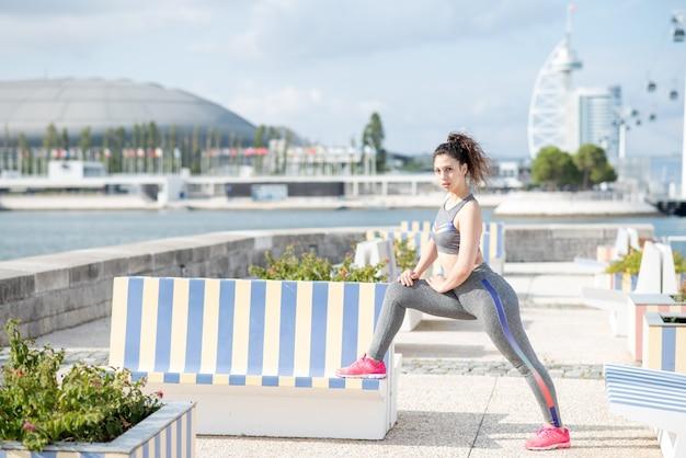 Menina que alonga a perna e usa o banco ao ar livre