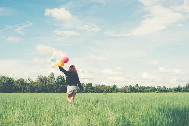 Menina que anda com balões coloridos