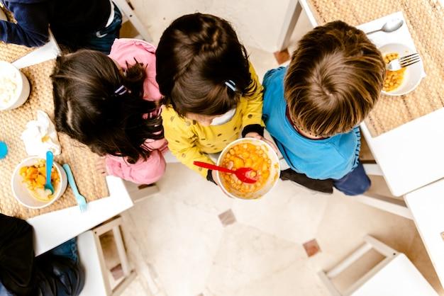 Menina que anda com uma bacia de guisado na sala de jantar de seu infantário, vista superior, com espaço da cópia.