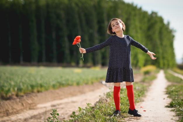 Menina que anda no campo da natureza que desgasta o vestido bonito