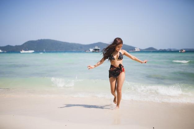 Menina que aprecia e que corre na praia.