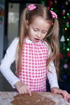 Menina que assa biscoitos de gengibre para o natal em casa