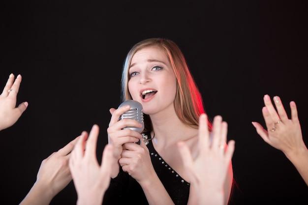 Menina que canta e mão levantada mãos do público