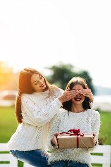 Menina que cobre os olhos com uma outra menina com um presente em suas mãos