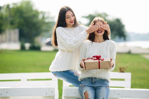 Menina que cobre os olhos com uma outra menina com um presente no colo