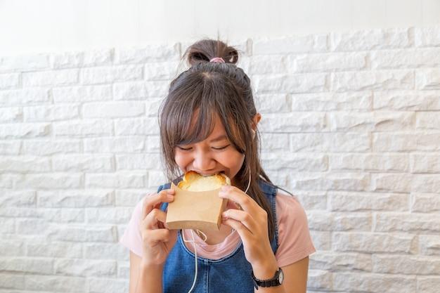 Menina que come a grade do pão do queijo.
