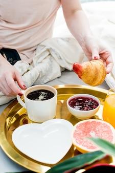 Menina que come o croissant no café da manhã na cama, serviço de hotel. café, geléia, croissant, suco de laranja, grapefruit, lichia.