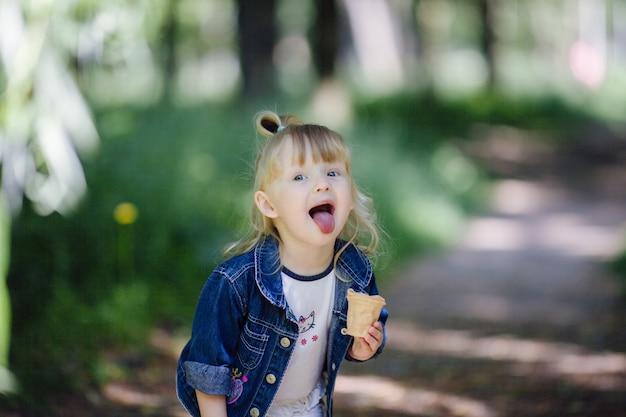 Menina que come um gelado e saindo a língua