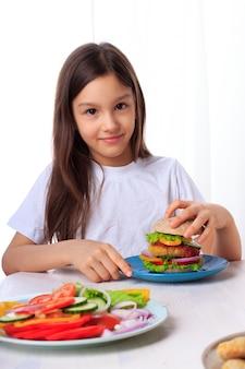 Menina que come um hamburguer veggie saudável do vegetariano com salada verde, os bolos da farinha do whole-whealt e os fritters do grão-de-bico isolados