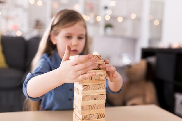 Menina que constrói torre de tijolos de madeira