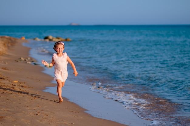 Menina que corre e que salta na costa de mar.