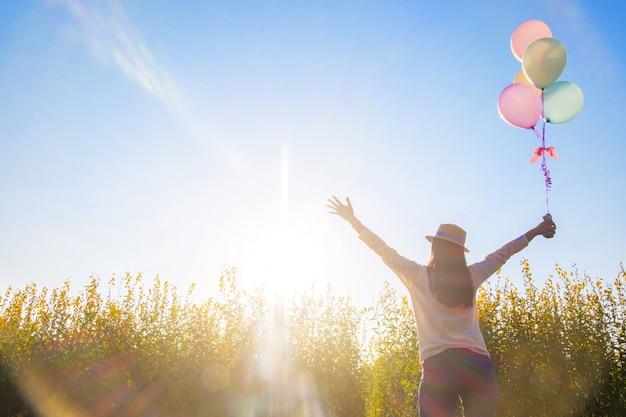 Menina que corre no campo dos balões florais amarelos ao pôr do sol. mulher feliz na natureza, conceito sobre a artilharia despreocupada e relaxar, efeito vintage