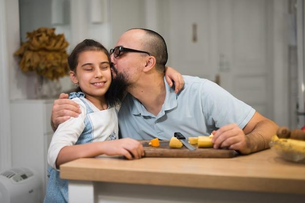 Menina que cozinha com um pai carinhoso e amoroso em uma cozinha moderna. pai jovem feliz com filha bonita na cozinha.