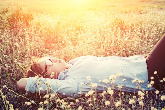 Menina que dorme em um campo de flores