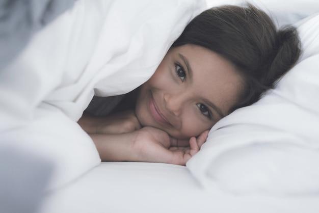 Menina que encontra-se sob o cobertor na cama branca.