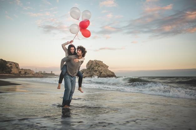 Menina que escala nas costas de seu namorado, segurando balões