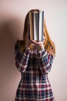 Menina que esconde o rosto com vários livros