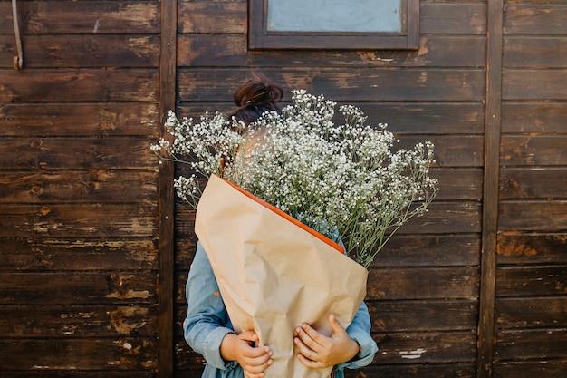 Menina que esconde o rosto por trás do buquê