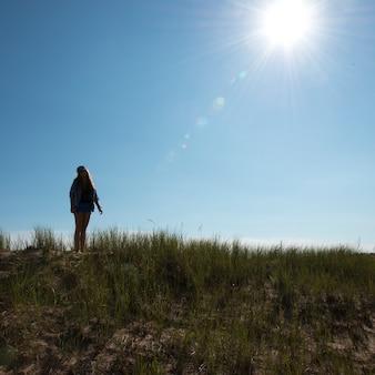 Menina que está na duna de areia gramínea sob a luz do sol brilhante na fuga de cavendish dunelands, frontões verdes,