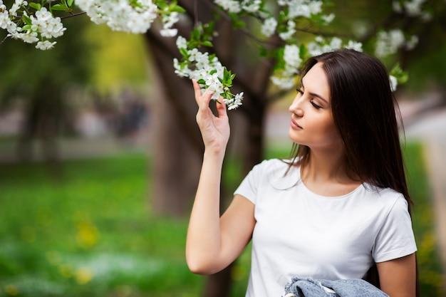 Menina que está sob a árvore de maçã de florescência no parque natural. conceito de moda. jovem elegante em roupas jeans, desfrutando de jardim florido em dia ensolarado de primavera. maquiagem de beleza natural. horizontal