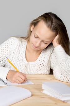 Menina que estuda em uma mesa de madeira