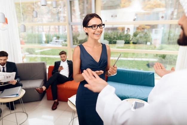 Menina que fala com homens de negócios árabes em um negócio.