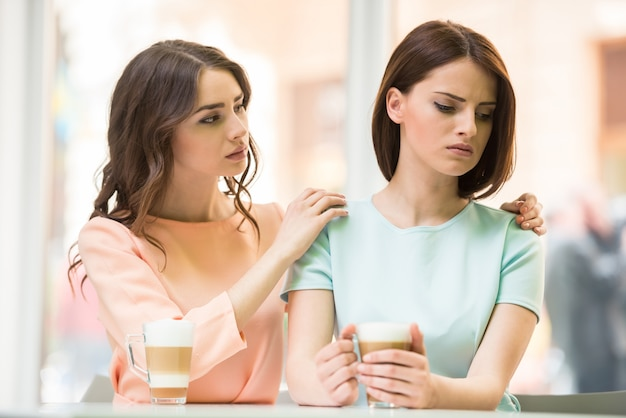 Menina que fala com seu amigo chateado e segurando seus ombros