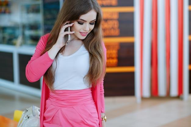 Menina que fala no telefone e olhando para o chão