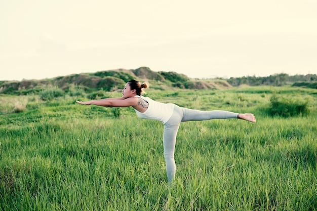 Menina que faz a ioga em uma perna