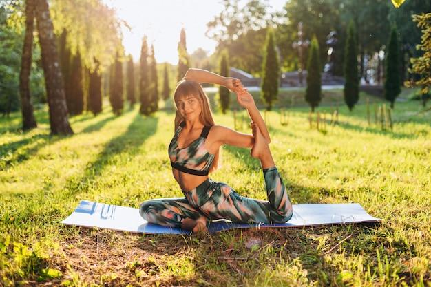 Menina que faz a ioga que senta-se na pose do pombo ao ar livre.