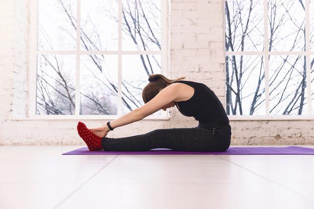 Menina que faz um asana que dobra-se para a frente com suas mãos para seus pés. sentado no chão