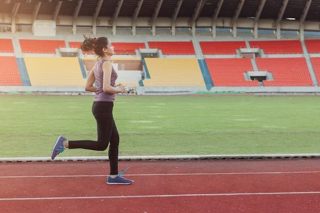 Menina que funciona em uma pista de atletismo