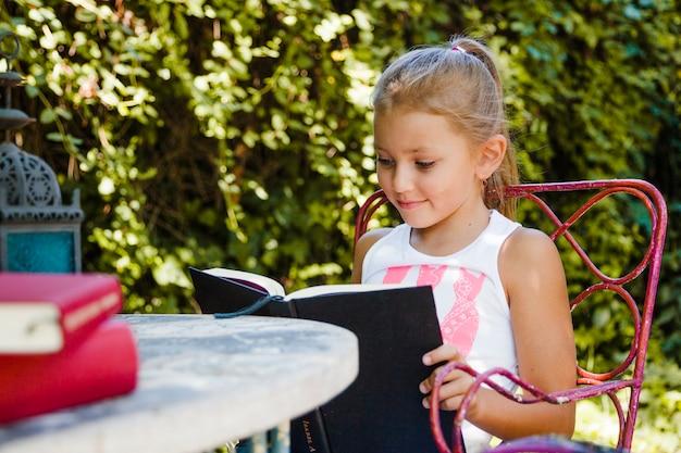 Menina que gosta de livro no jardim