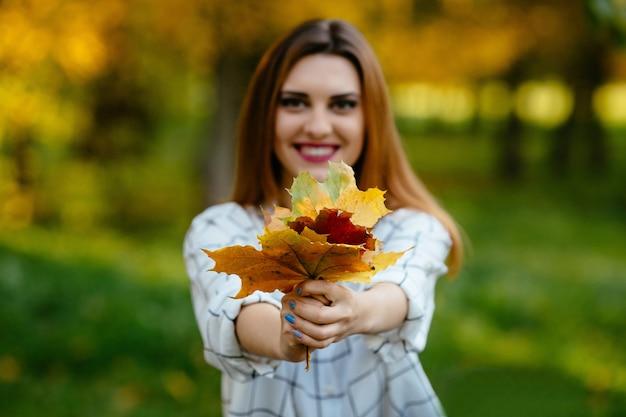 Menina que guarda as folhas de outono em ambas as mãos no parque.