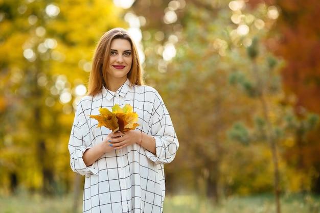 Menina que guarda as folhas de outono no parque.