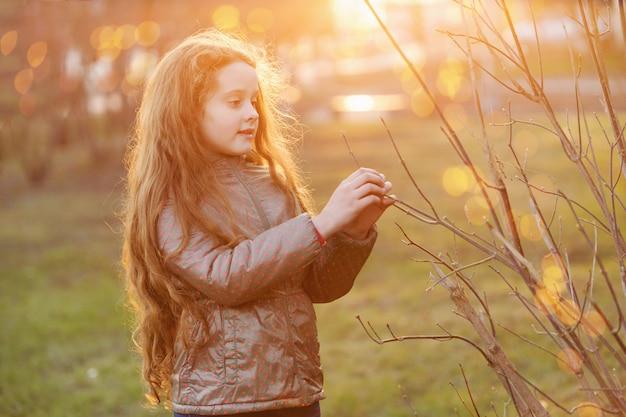 Menina que guarda o ramo de árvore verde novo na luz solar.