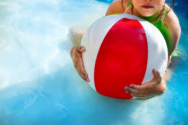 Menina que joga com a bola na piscina ao ar livre na água em férias de verão